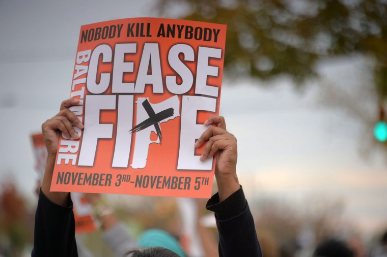A participant holds a placard during the second Baltimore Cease Fire weekend, held at Edmondson Village Shopping Center. (Karl Merton Ferron / Baltimore Sun Staff)
