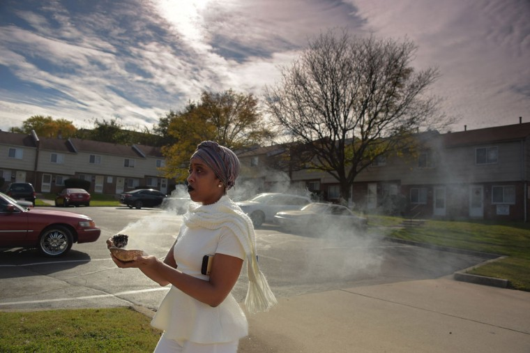 Timing her smudging to begin twelve hours after the expiration of the deceased, Ellen Gee uses smoldering sage for smudging at the spot where witnesses claim a victim was fatally shot at an overnight shooting on the 2800 block Elgin Avenue during the second Baltimore Cease Fire weekend. Washington, D.C. Metropolitan Police Sgt. Tony Mason Jr. was shot, along with a female just after midnight. Sgt. Mason later died. (Karl Merton Ferron / Baltimore Sun Staff)