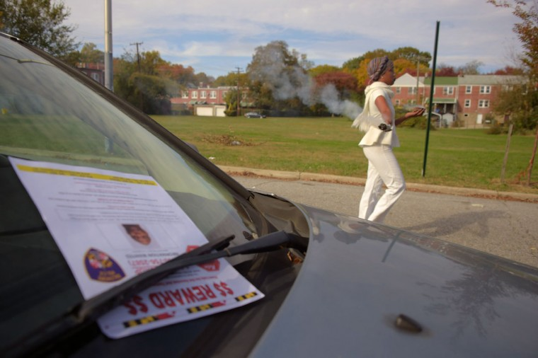 A flier sits on a car windshield as Ellen Gee uses smoldering sage for smudging at the spot where witnesses claim a victim was fatally shot at an overnight shooting on the 2800 block Elgin Avenue during the second Baltimore Cease Fire weekend. Washington, D.C. Metropolitan Police Sgt. Tony Mason Jr. was shot, along with a female just after midnight. Sgt. Mason later died. (Karl Merton Ferron / Baltimore Sun Staff)