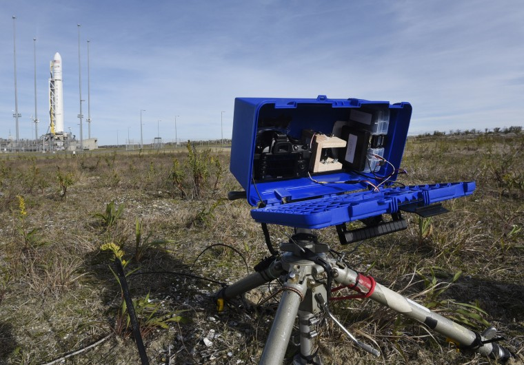 A modified toolbox, mounted on a tripod, serves as a protective housing for a digital still camera, GoPro video camera and electronics to photograph the launch remotely from about 200 yards from the launchpad. The tripod is staked into the ground to keep it from being knocked over by weather or the blast of the rocket. (Dylan Slagle/Baltimore Sun Media Group)