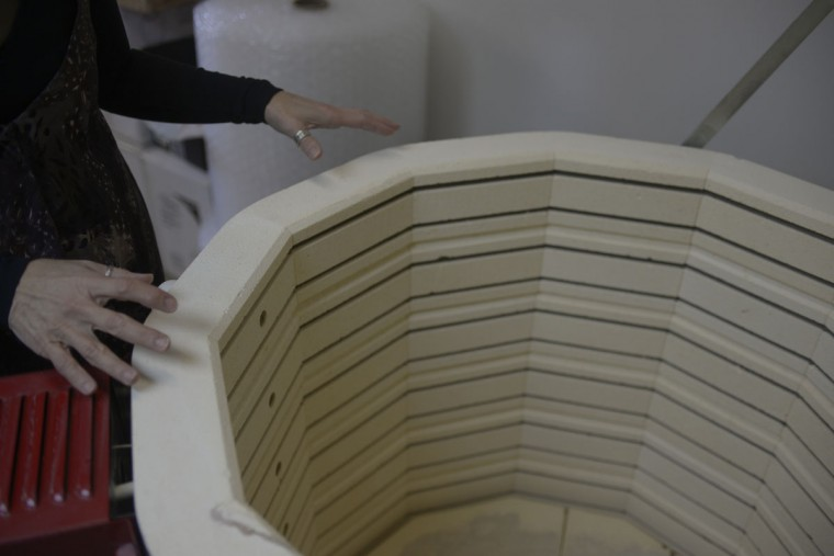 Renee Arambiges stands by the kiln she uses to fire her clay sculptures. (Christina Tkacik/Baltimore Sun)