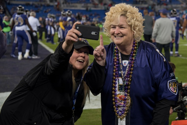 A fan records a pregame video on the sidelines with a member of the Ravens' staff while players warm up in the background. (Ulysses Munoz/Baltimore Sun)