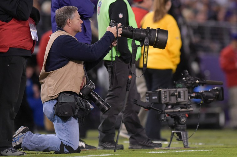 Lloyd checks out one of his shots on the sidelines between plays. (Ulysses Munoz/Baltimore Sun)