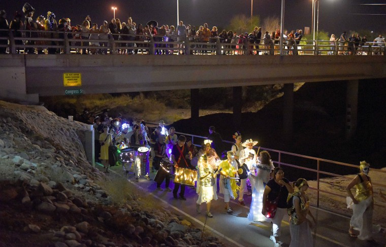 Spectators line the Congress Street bridge as revelers emerge from the Santa Cruz River Walk during Tucson's All Souls Procession. (Jerry Jackson/Baltimore Sun)