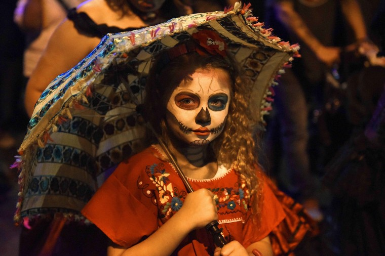 A young girl walks in Tucson's All Souls Procession. Despite some scary costumes the event is family friendly with participants of all ages. (Jerry Jackson/Baltimore Sun)