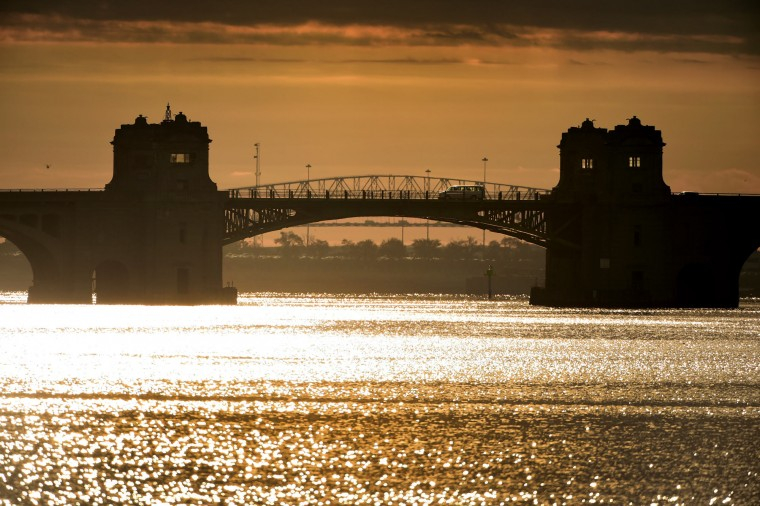 The Francis Scott Key Bridge (background span) barely rises in the background as a van traverses the double span, crossing the Middle Branch Patapsco River at sunrise. The Vietnam Veterans Memorial Bridge, known by many as the Hanover Street Bridge, links Baltimore and Port Covington with Cherry Hill, Brooklyn and Curtis Bay.(Karl Merton Ferron / Baltimore Sun)