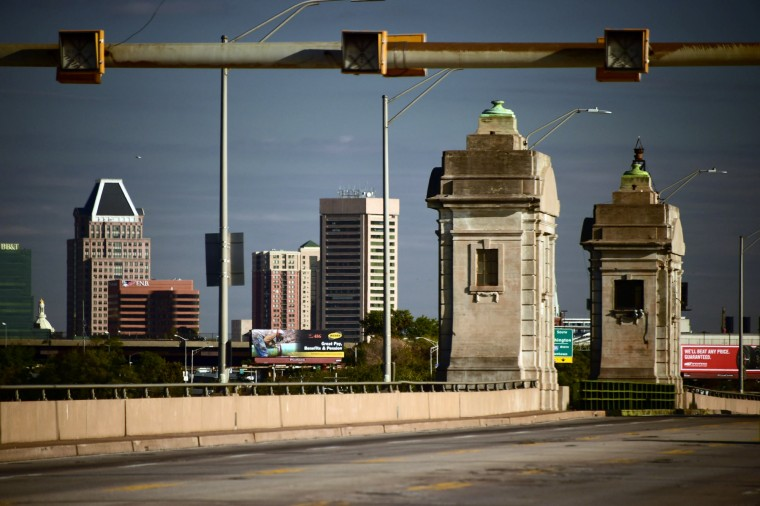 The drawbridge watchtower rises beneath lane signals in front of the city skyscrapers in a study of the Vietnam Veterans Memorial Bridge, known by many as the Hanover Street Bridge, which links Baltimore and Port Covington with Cherry Hill, Brooklyn and Curtis Bay. (Karl Merton Ferron / Baltimore Sun)