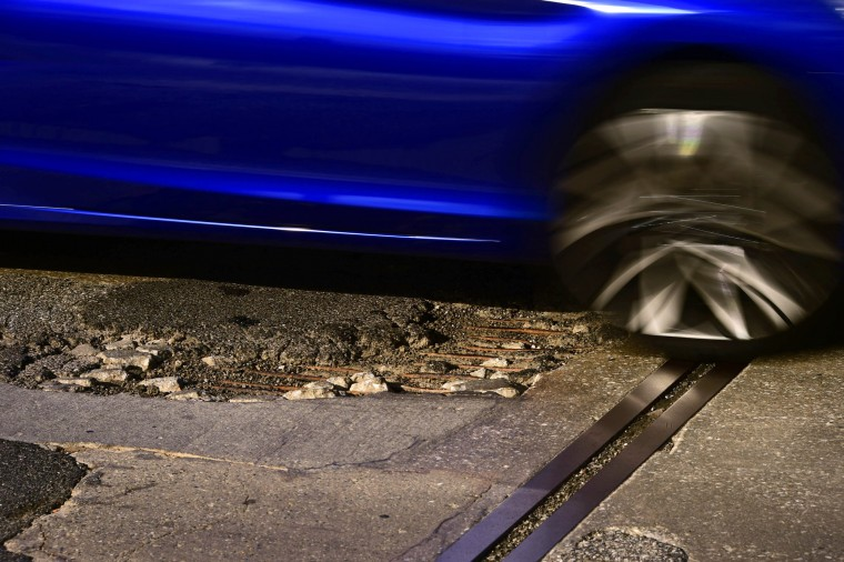 A car strikes a pothole which reveals shredded asphalt and concrete to show rusting rebar in a study of the Vietnam Veterans Memorial Bridge, known by many as the Hanover Street Bridge. (Karl Merton Ferron / Baltimore Sun)