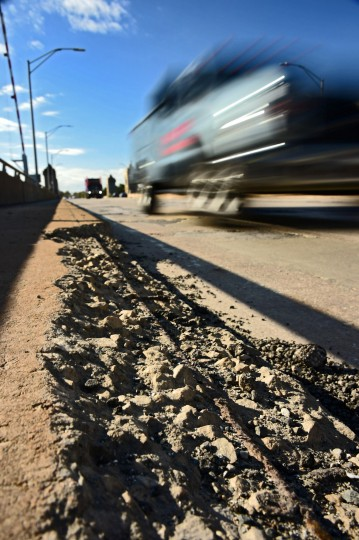 Traffic moves past eroding concrete and rebar on the pedestrian walkway on Vietnam Veterans Memorial Bridge, known by many as the Hanover Street Bridge, which links Baltimore and Port Covington with Cherry Hill, Brooklyn and Curtis Bay. (Karl Merton Ferron / Baltimore Sun)