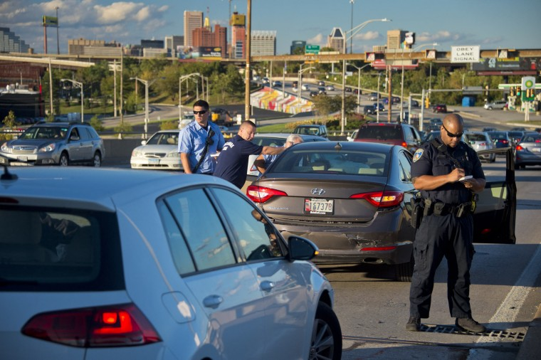 The city center looms above, while first responders watch oncoming traffic (left) as a driver is tended to, while a Baltimore Police officer documents an afternoon crash in a study of the Vietnam Veterans Memorial Bridge, known by many as the Hanover Street Bridge, which links Baltimore and Port Covington with Cherry Hill, Brooklyn and Curtis Bay. (Karl Merton Ferron / Baltimore Sun)