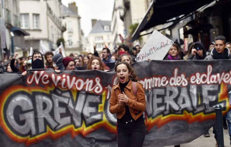 A young woman shouts slogans in front of a banner as thousands of people demonstrate on March 9, 2016 in Nantes, western France, as part a nationwide day of protest against proposed labour reforms. France faced a wave of protests against deeply unpopular labour reforms that have divided an already-fractured Socialist government and raised hackles in a country accustomed to iron-clad job security. (AFP / Loic Venance)