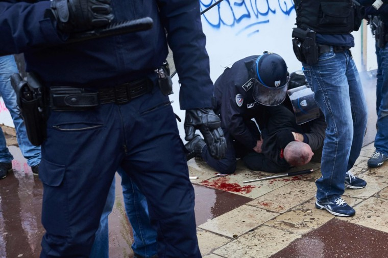 Police detain a protester during clashes at a demonstration on March 9, 2016, in Lyon, central-eastern France, as part of a nationwide day of protest against proposed labour reforms. France faced a wave of protests on March 9 against deeply unpopular labour reforms that have divided an already-fractured Socialist government and raised hackles in a country accustomed to iron-clad job security. (AFP / Jean-Philippe Ksiazek)